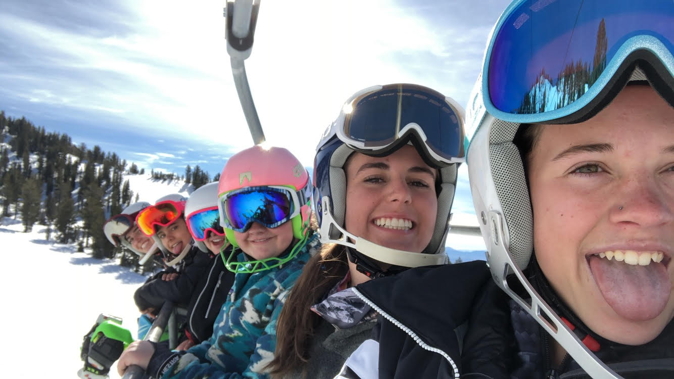 Soph Maclean, Gigi Taylor, and more of the ski team smile big on the chair lift.