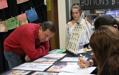 Mr. Rossolo decides which picture he wants to purchase as Valentina Ossio-Marin looks on.