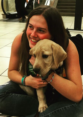 Mikaela Lang cuddles with Ode, her service-dog-in-training, upon her return to the United States from a year-long foreign exchange program in Luján, Argentina.